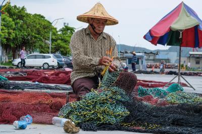 被海風鏤刻出 滿面風霜的漁工們,在漁港邊熟練靈巧地補著破網。(莊坤儒攝)