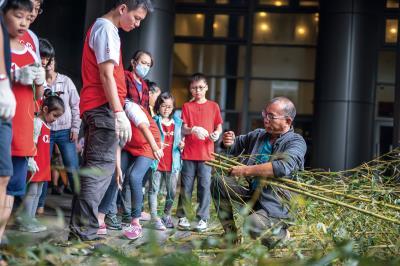 王銘祥帶領大人小孩將竹叢綁成軟絲產房,並藉機宣導保育觀念。(林旻萱攝)