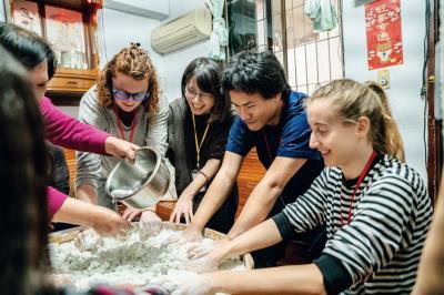 Minerva Schools學生在蟾蜍山社區老師葉媽的教導下, 製作客家菜草仔粿。(台灣大學國際事務處提供)
